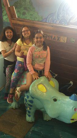 kids sitting on dinosaur toy